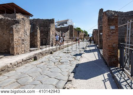 Pompeii, Company, Italy - June 25, 2019: Typical Street Of Ancient Pompeii. Tourists Visit The Ruins
