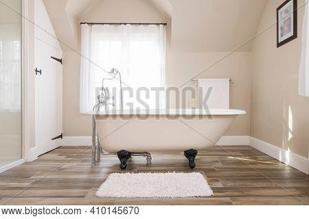 Bathroom Interior, Luxury Modern Bathroom Design With Roll Top Bathtub And A Window In The Backgroun