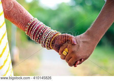 Indian Married Couple Holding Hands (with Henna And Bangles On Hands)