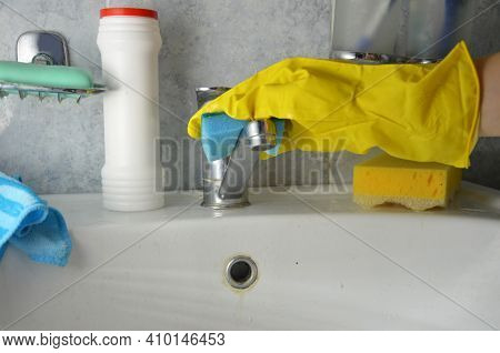 Housewife Cleaning Bathroom Tap And Shower Tap. Maid In Yellow Protective Gloves Washing Dirty Bath