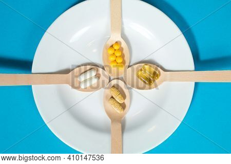 Vitamins On Wooden Spoons In A White Plate On A Blue Background. Multivitamin Set For Every Day. The