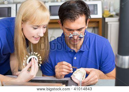 Two Dental Technicians Choosing The Right Colour For Dental Porcelain