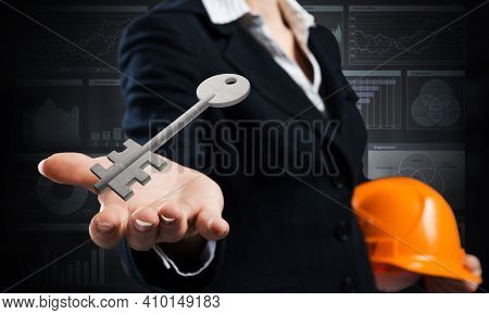 Real Estate Agent Holds In Palm 3d Key From House Lock. Woman Realtor In Business Suit With Safety H