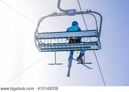 Ski Lift On The Slop In Mountain Ski Resort With Skier On The Lift. Cableway For Tourists, Skiers An