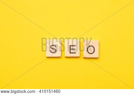 Word Seo Made From Wooden Letters On Yellow Background. Search Engine Optimisation.