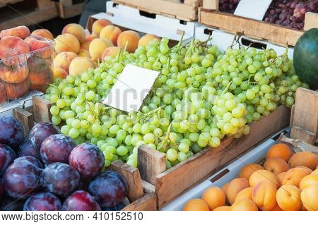 Bunches Of Grapes , Peaches And Plums On The Counter. Green, Red Bunches Of Ripe Grapes Are Laid Out