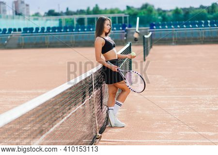 Sports Fashion. Beautiful Woman On Tennis Court. Portrait Of Stylish Sexy Girl In Black Trendy Sport