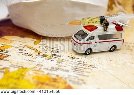 Miniature People Stand On Ambulance Car With Medical Mask And Syringe Of Covid-19 Vaccine . Vaccine
