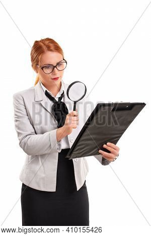 A Portrait Of A Young Businesswoman Looking At A Document On A Clipboard Through A Magnifying Glass,