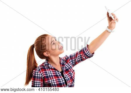 Beautiful Smiling Casual Young Girl Taking A Selfie With Her Tongue Out, Isolated On A White Backgro