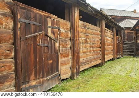 Rustic Cattle Shed With Large Gates In The Farmstead's Farmyard.