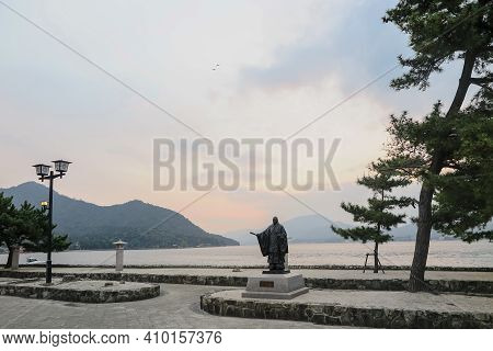 The Man Statute Stand In Front Next The Tree On The Mountain And Lake View In Sunset Time, The Sight