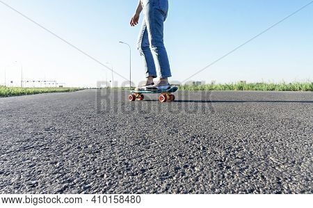 Skater Caucasian Young Woman Legs In Blue Jeans Skateboarding On The Road In Summer, Active Lifestyl