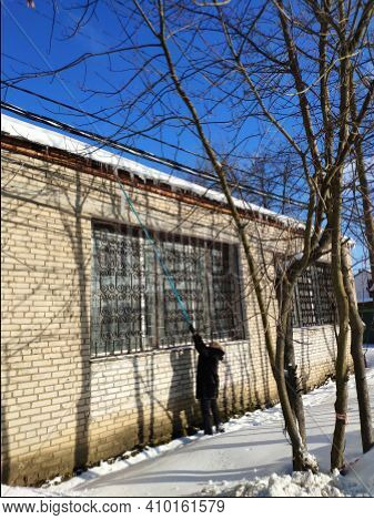 Moscow, Russia - 05 February 2020:: Woman Knocks Ice And Icicles From The Roof Of A House. Cold Wint