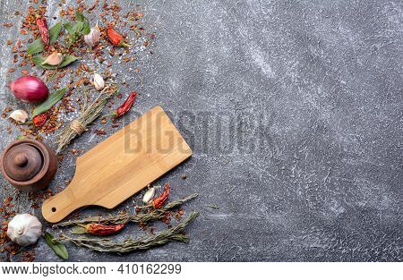 Dark Culinary Background With A Wooden Chopping Board Along With Garlic, Rosemary, Bay Leaves, Peppe