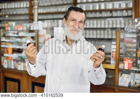 Happy Pharmacist Day Concept. Portrait Of Happy Senior Man Pharmacist Wearing Lab Coat, Holding In H