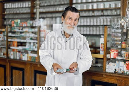 Drug Store, Disease Treatment, Pills And Tablets Concept. Senior Bearded Male Pharmacist Smiling At