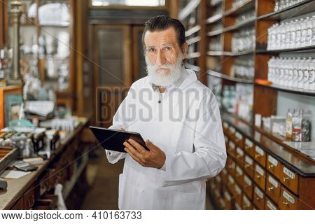 Pharmacist In Vintage Old Pharmacy. Handsome Elderly Bearded Man Pharmacist With Digital Tablet In A