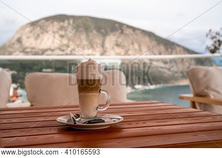 A Glass Of Latte Macchiato On The Terrace Of A Summer Cafe With Views Of The Landscape, Mountains An