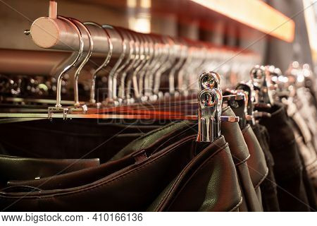 Clothes On Hangers In A Store. Leather Skirts On Hangers In The Store.metal Clothes Hanger, Warm Lig