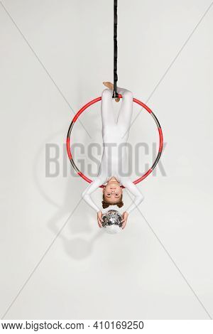 Little Child Girl Gymnast In White Sportwear Shows An Acrobatic Performance With Mirror Ball On An A