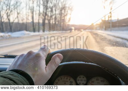 The Driver Hand On The Steering Wheel Of A Car That Is Driving On A Slippery Winter Road And The Ray