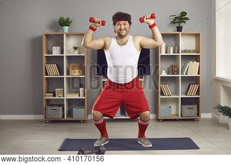 Funny Chubby Man Exercising With Dumbbells Standing On Fitness Mat In Living-room