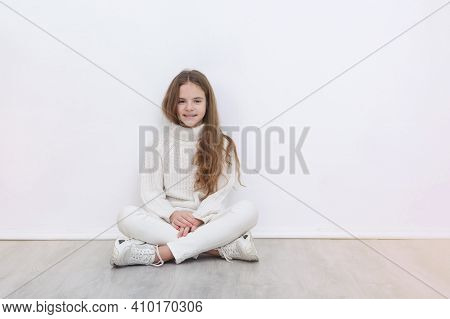 1 White Girl 10 Years Old In A White Sweater, Jeans And Sneakers Sits On The Floor Against A White W