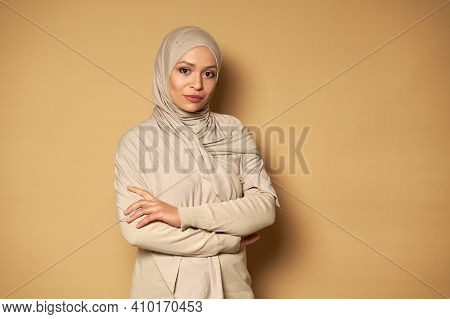 Confident Portrait Of Serene And Successful Beautiful Arab Muslim Woman Posing With Crossed Arms On