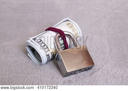 Bundle Of Dollars Under Lock On A Gray Background