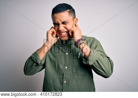 Young brazilian man wearing casual shirt standing over isolated white background covering ears with fingers with annoyed expression for the noise of loud music. Deaf concept.