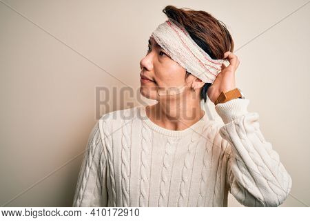 Young handsome chinese man injured for accident wearing bandage and strips on head confuse and wondering about question. Uncertain with doubt, thinking with hand on head. Pensive concept.