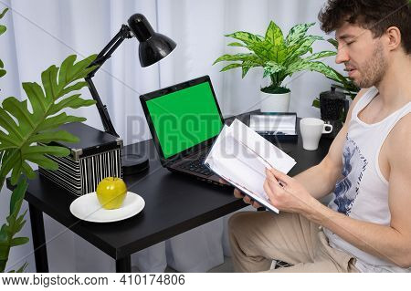 A Young Employee Flicks Through The Calendar In His Hands To Check The Amount Of Information Stored.
