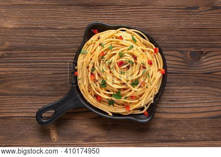 Homemade Pasta With Seasonings And Sauce In A Frying Pan On A Wooden Background. Top View.