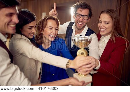 A manager and a team at the hallway are happy about won the trophy at a business conference at the hotel. Hotel, business, people