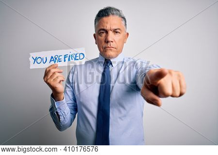 Middle age grey-haired man fired with problems holding paper with you are fired message pointing with finger to the camera and to you, hand sign, positive and confident gesture from the front