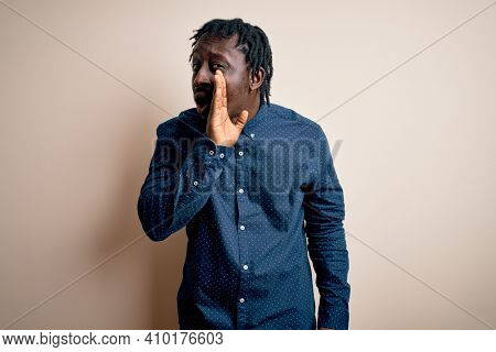 Young handsome african american man wearing casual shirt standing over white background hand on mouth telling secret rumor, whispering malicious talk conversation