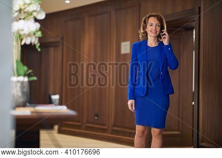 An elegant and successful business woman standing and talking on a phone at the hotel hallway. Hotel, business, people