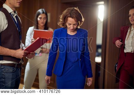 A female manager having a serious talk with the team in an unpleasant atmosphere at the hotel hallway. Hotel, business, people