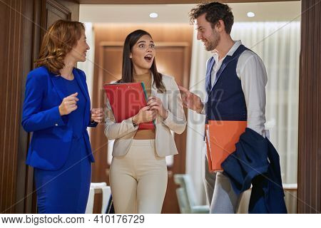 A group of business people standing and chatting in a pleasant atmosphere at the hotel hallway. Hotel, business, people