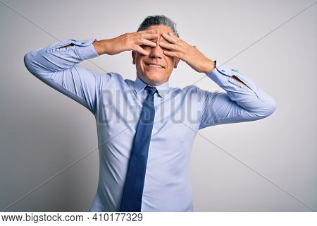 Middle age handsome grey-haired business man wearing elegant shirt and tie covering eyes with hands smiling cheerful and funny. Blind concept.