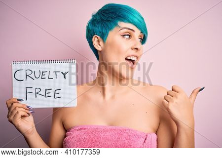 Young woman with blue fashion hair showing cruelty-free cosmetics message pointing and showing with thumb up to the side with happy face smiling