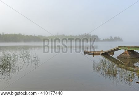 Morning Mist On A Quiet Lakeshore On Seagull Lake Inthe Boundary Waters In Minnesota