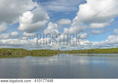 Puffy Clouds Over The Great North Woods On Alpine Lake In The Boundary Waters In Minnesota