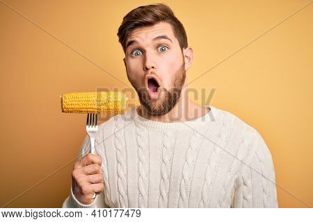 Young blond vegetarian man with beard and blue eyes holding fork with fresh cob corn scared in shock with a surprise face, afraid and excited with fear expression