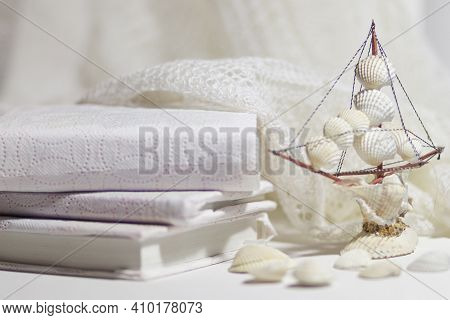Books In A White Cover And A Figure Of A Sailboat Made Of White Shells On A White Background. The Co