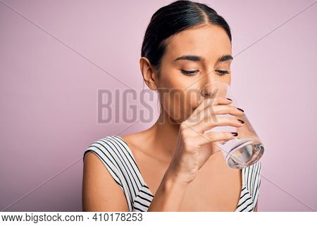 Young beautiful brunette woman drinking glass of healthy water to refreshment standing over isolated pink background