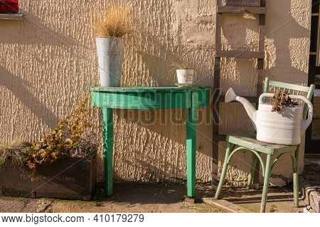 A White Watering Can On A Green Chair And A Dried Flower. Green Table With A Flower In A Pots And A