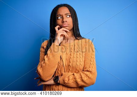 Young african american woman wearing casual yellow sweater standing over blue isolated background with hand on chin thinking about question, pensive expression. Smiling with thoughtful face. Doubt