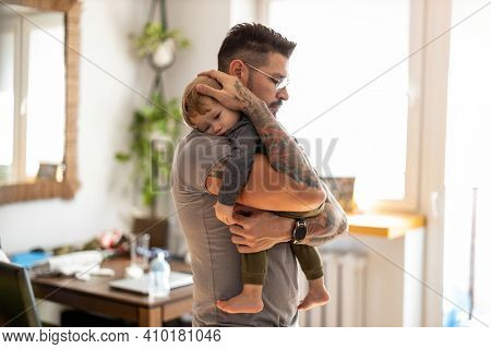 Dad putting to sleep baby boy in his arms